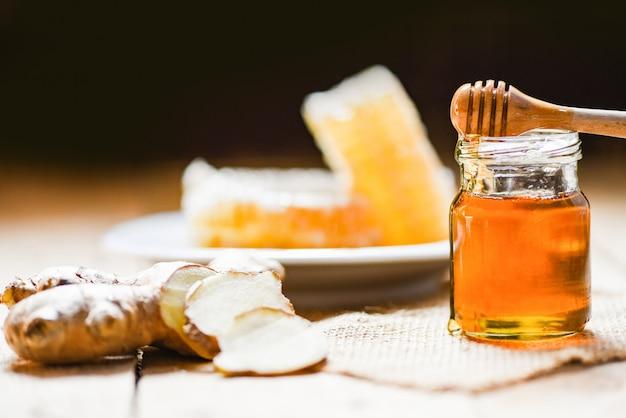 Miel en tarro con cucharón de miel, jengibre y en madera y nido de abeja