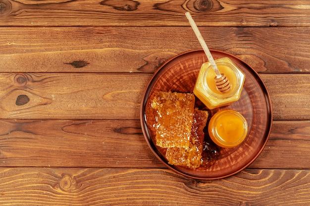 Miel en tarro con cucharón de miel en madera vintage