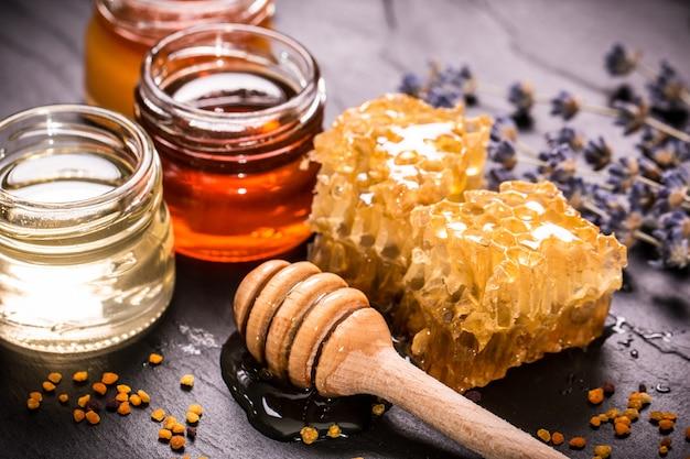 Miel en tarro con cucharón de miel sobre piedra negra