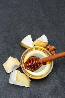 Miel y trozos de queso brie sobre fondo de hormigón oscuro