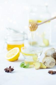 La miel se vierte en una bebida de jengibre en una taza. raíz de jengibre, miel en un frasco, limón sobre una mesa blanca.