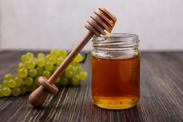 Miel de vista frontal en un frasco con una cuchara de madera y uvas verdes y sobre un fondo de madera