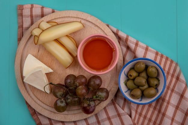 Miel de vista superior con uvas y queso en un soporte con aceitunas en una toalla a cuadros