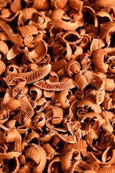 Migajas rotas de delicioso chocolate con leche dulce durante la preparación de postres, detalles de dulces en la mesa de madera