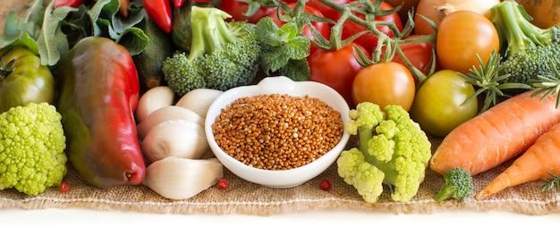 Mijo rojo crudo en un recipiente con verduras aislado en blanco