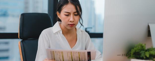 Milenaria joven empresaria china trabajando estresarse con el problema de investigación del proyecto en el escritorio de la computadora en la sala de reuniones en la pequeña oficina moderna concepto de síndrome de burnout ocupacional de personas de asia.
