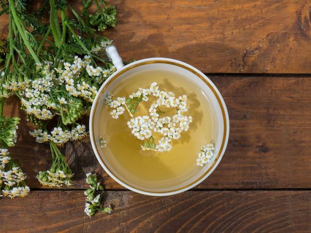 Milenrama de plantas medicinales, una taza con una decocción de flores de milenrama sobre un fondo de madera