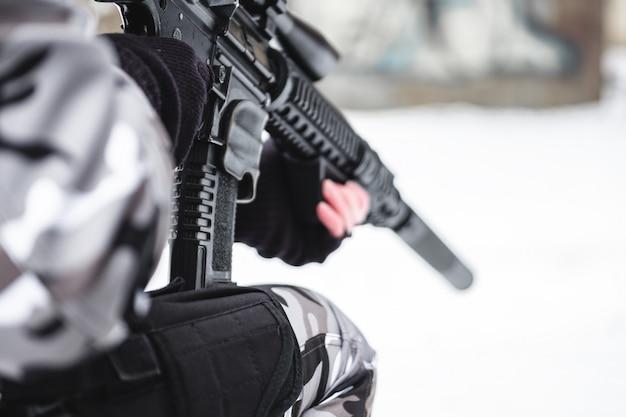 Un militar en camuflaje invernal con un rifle se está preparando para un ataque.