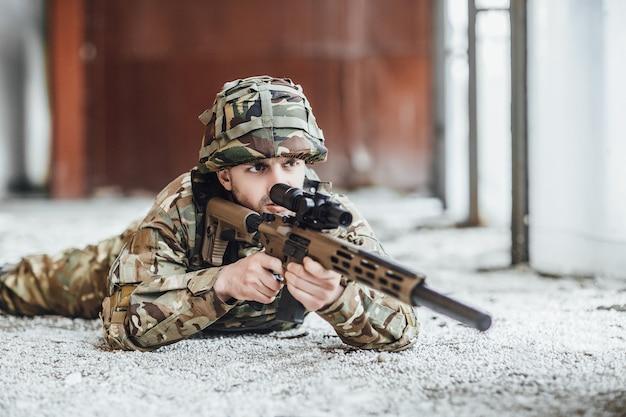Militar en la forma se sostiene en manos de un rifle grande.