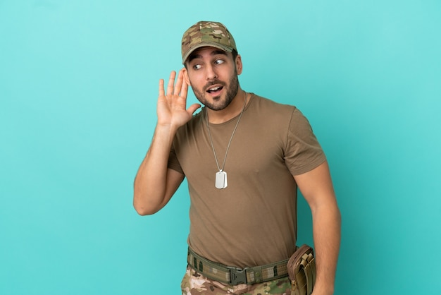 Militar con placa de identificación sobre aislado sobre fondo azul escuchando algo poniendo la mano en la oreja