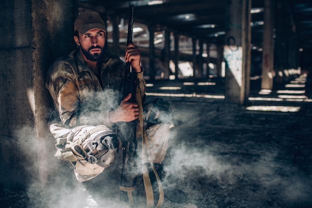 El militar está sentado detrás de la columna y sostiene el rifle cerca de su cuerpo. él está sentado muy callado. guy está esperando. no tiene prisa.
