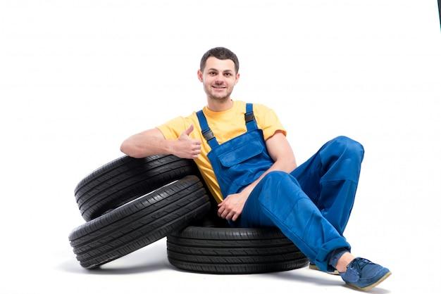 Militar sentado sobre neumáticos, fondo blanco.