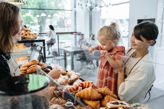 Mimada con la elección de la niña recogiendo unos croissants en una panadería, mientras la madre la sostiene en las manos. cajero sonriendo a su madre.