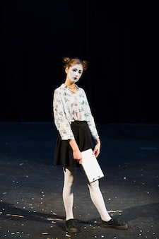 Mime femenino con manuscrito de pie en el escenario