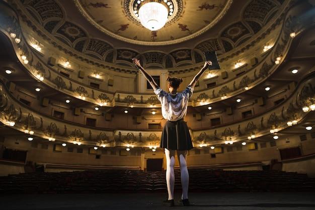 Mime femenino de pie en el escenario levantando los brazos