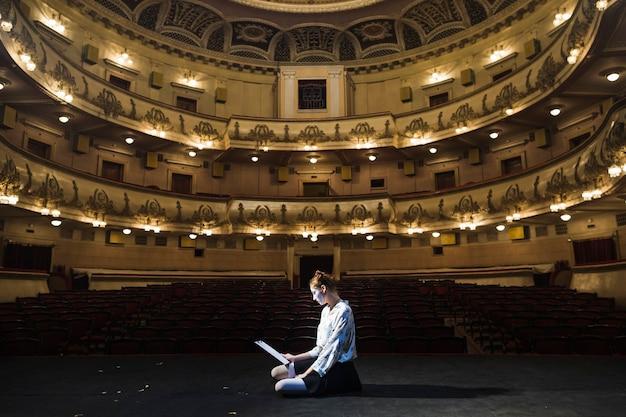 Mime femenino sentado en el escenario leyendo el manuscrito