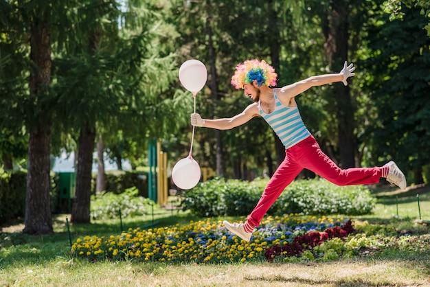 Mime salta en el parque con globos.