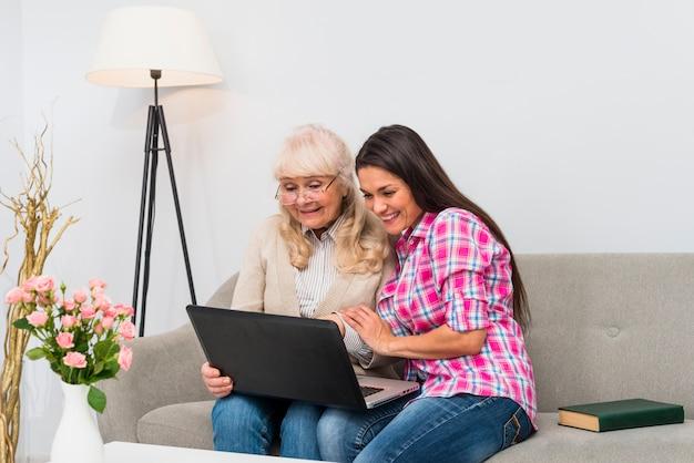 Mime y su hija joven que se sienta junto en el sofá que mira el ordenador portátil