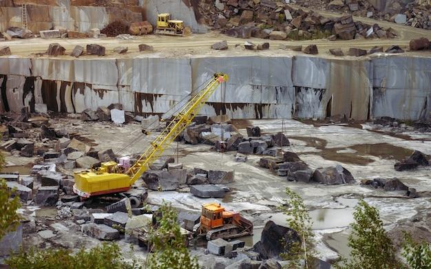 Mina de piedra de granito con excavadoras de equipo pesado cargando rocas crudas