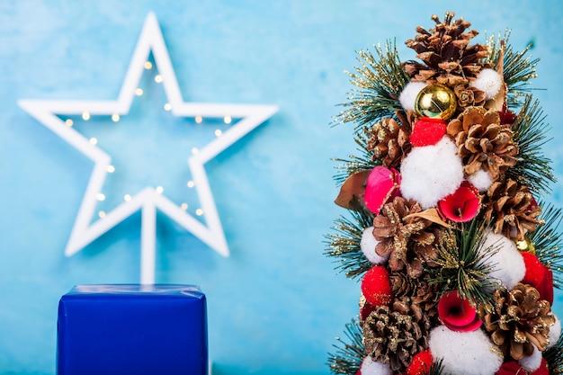 Mini árbol de navidad sobre fondo azul en foto de estudio. estacional y festivo