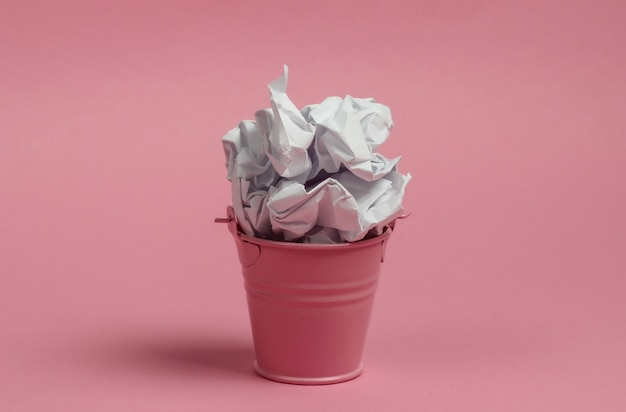Mini balde con papel arrugado sobre un fondo rosa.