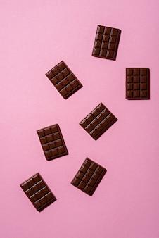 Mini barras de chocolate sobre un fondo rosa