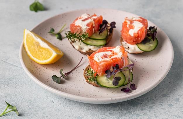 Mini bocadillos abiertos con salmón ahumado, queso crema, pepino y microgreen sobre pan de centeno.