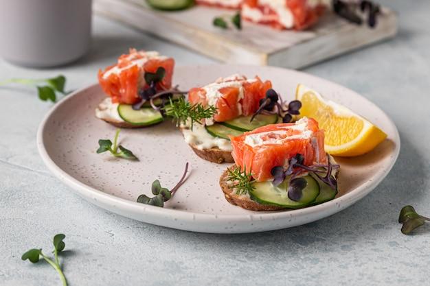 Mini bocadillos abiertos de salmón, queso crema, pepino y microgreen sobre pan de centeno.