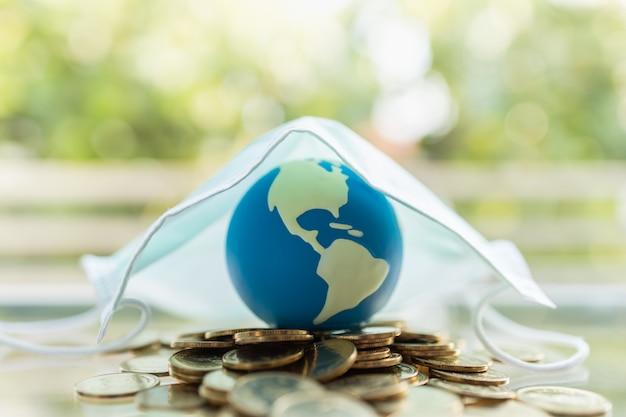 Mini bola del mundo en pila de monedas de oro bajo mascarilla quirúrgica con espacio de copia.