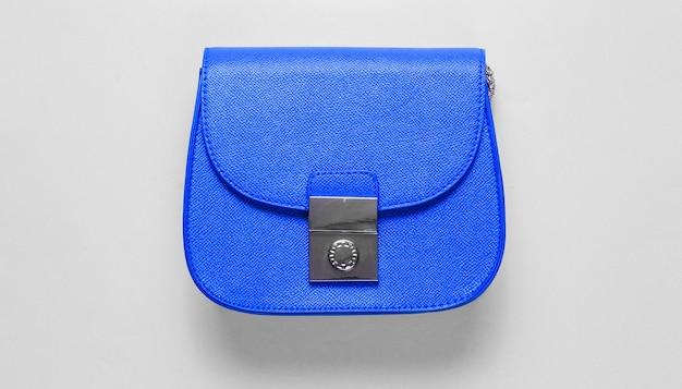 Mini bolso de piel azul sobre fondo azul. concepto de moda minimalista. vista superior