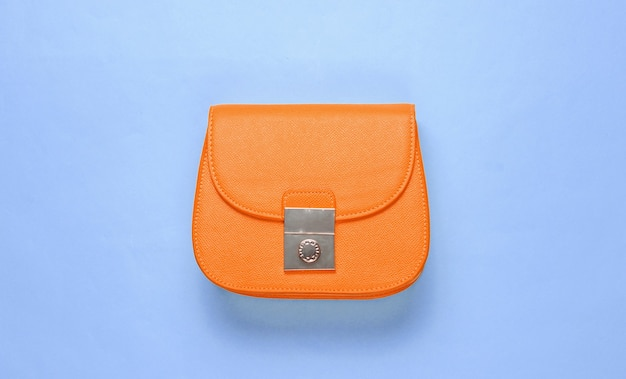 Mini bolso de piel naranja sobre fondo azul. concepto de moda minimalista. vista superior