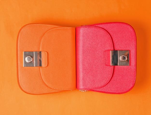 Mini bolsos de cuero rojo y naranja sobre fondo amarillo. concepto de moda minimalista. vista superior