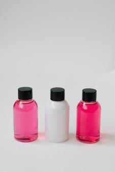 Mini botellas de color rosa y blanco con cosméticos para el cuidado del cuerpo o cabello sobre fondo blanco.