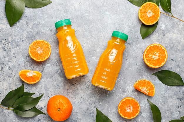 Mini botellas de plástico de jugo de naranja orgánico con naranjas y mandarinas crudas