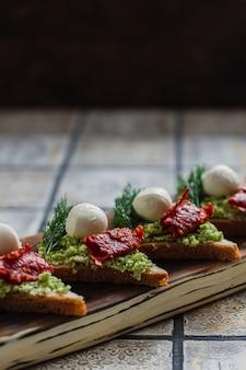 Mini bruschetta de canapés triangulares con aguacate, mozarella y tomates secos en el tablero rústico sobre el fondo de azulejos vintage.