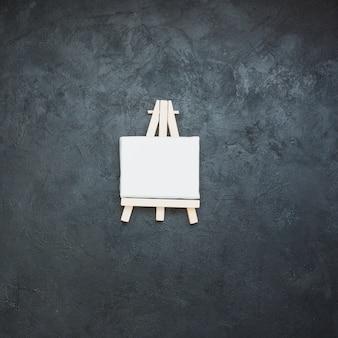 Mini caballete blanco en blanco sobre superficie de pizarra negra