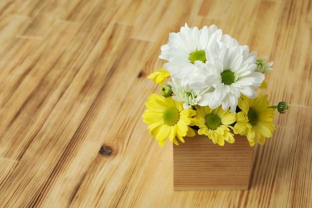 Mini caja con crisantemos sobre fondo de madera.