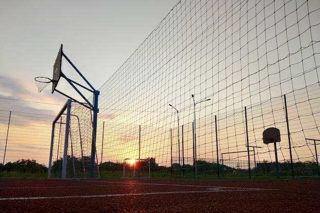 Mini cancha de fútbol y baloncesto al aire libre con portón de pelota y canasta rodeada con una alta valla protectora.