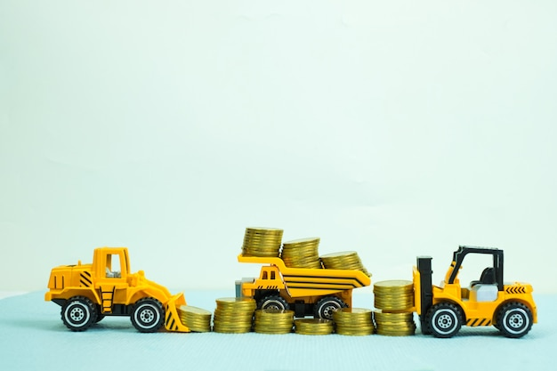 Mini carretilla elevadora bulldozer camión y máquina de rodillos de carretera con pila de monedas