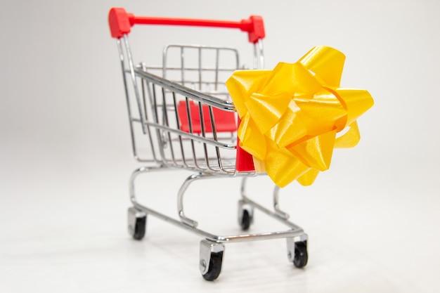 Mini carrito de la compra de hierro realista con piezas de plástico con un lazo navideño plateado.