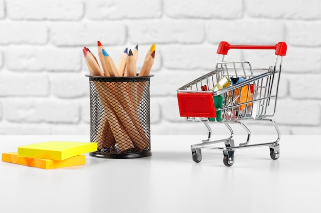 Mini carrito de compras con bolígrafos y lápices multicolores