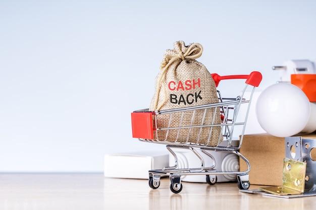 Mini carrito de compras con bolsa de devolución de efectivo y productos en la mesa.