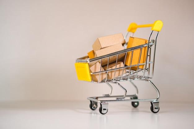 El mini carrito de compras contiene una caja de papel que utiliza como concepto de comercio electrónico, compras en línea y marketing comercial