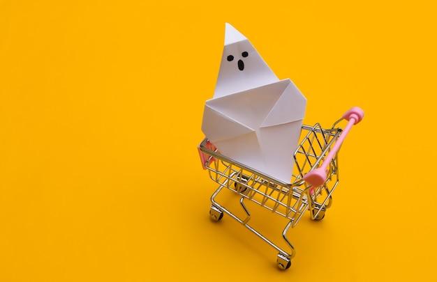 Mini carrito de compras con fantasma de origami sobre un fondo amarillo. tema de halloween