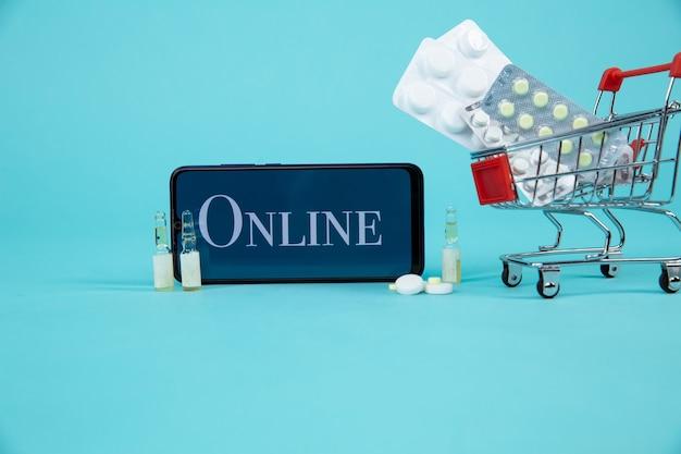 Mini carrito de compras lleno de remedios homeopáticos en el fondo de la computadora portátil. concepto de compras online homeopatía e internet.