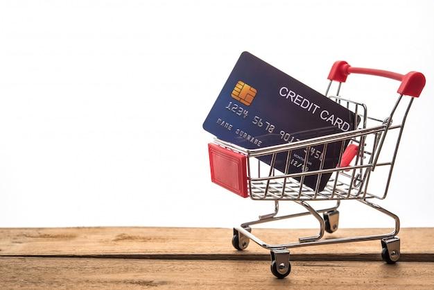 Mini carrito de compras en la mesa para el trabajo y tarjeta de crédito para el trabajo y el concepto de compras en línea