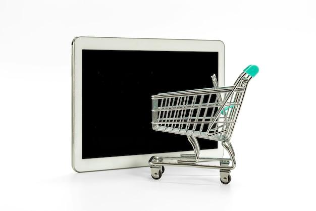 Mini carrito de compras y tableta digital con pantalla en negro aislado en blanco, concepto de compras en línea