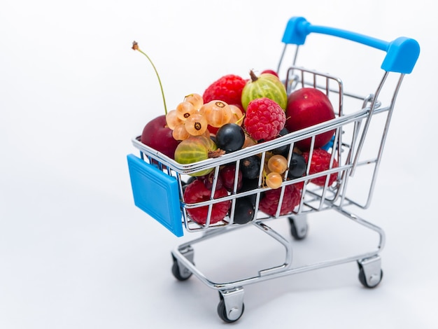 Mini carrito de supermercado lleno de bayas de vitamina frescas aisladas en blanco.