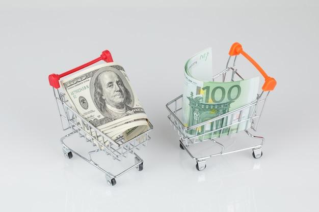 Mini carritos de compras con billetes de dólar y euro, concepto de dinero