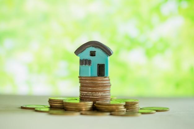 Mini casa en pila de monedas con desenfoque verde.
